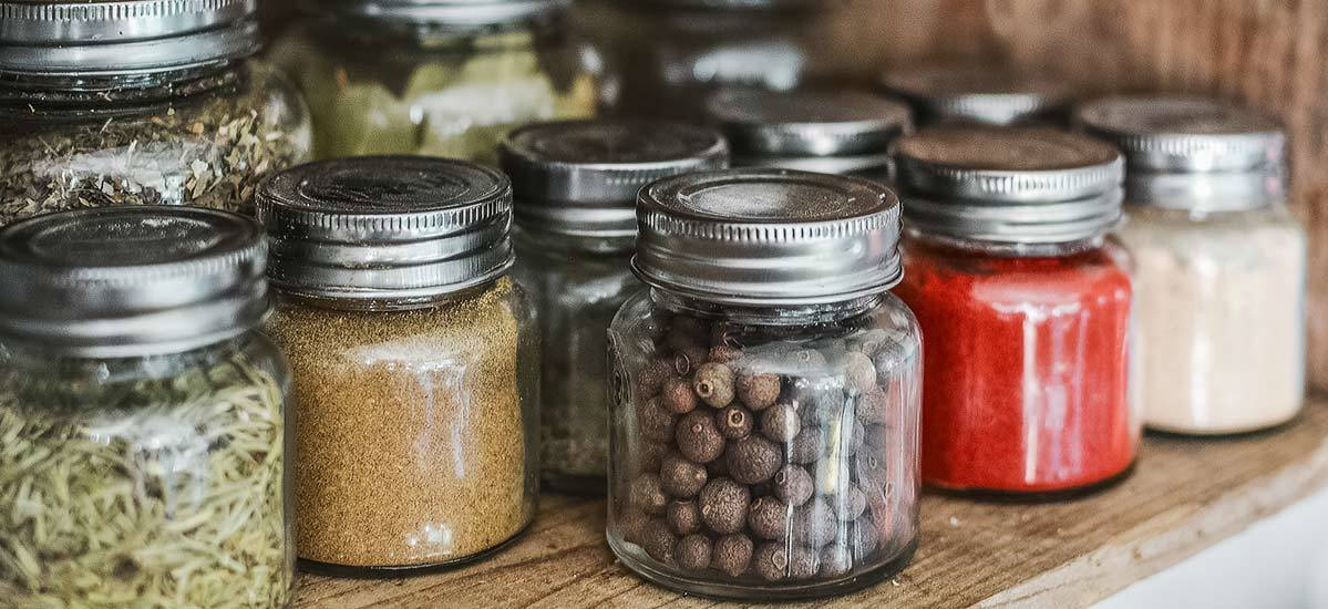 Small glass jars with silver caps filled with spices, grains, and other food.