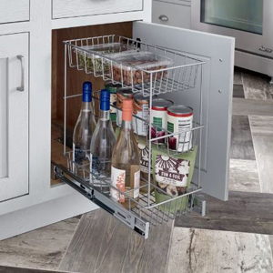 Three-tier compact kitchen cabinet pull-out drawer placed inside of a white cabinet and filled with wine bottles and canned food. photo