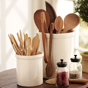 White ceramic container on a dark wooden table holding wooden kitchen tools. photo