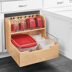 Wooden organizer for food storage containers placed in a white cabinet filled with red lids for clear tupperware. photo