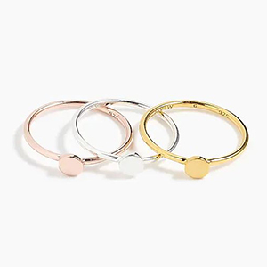 Stackable rings in rose gold, gold, and silver with simple design featuring a small circle photo