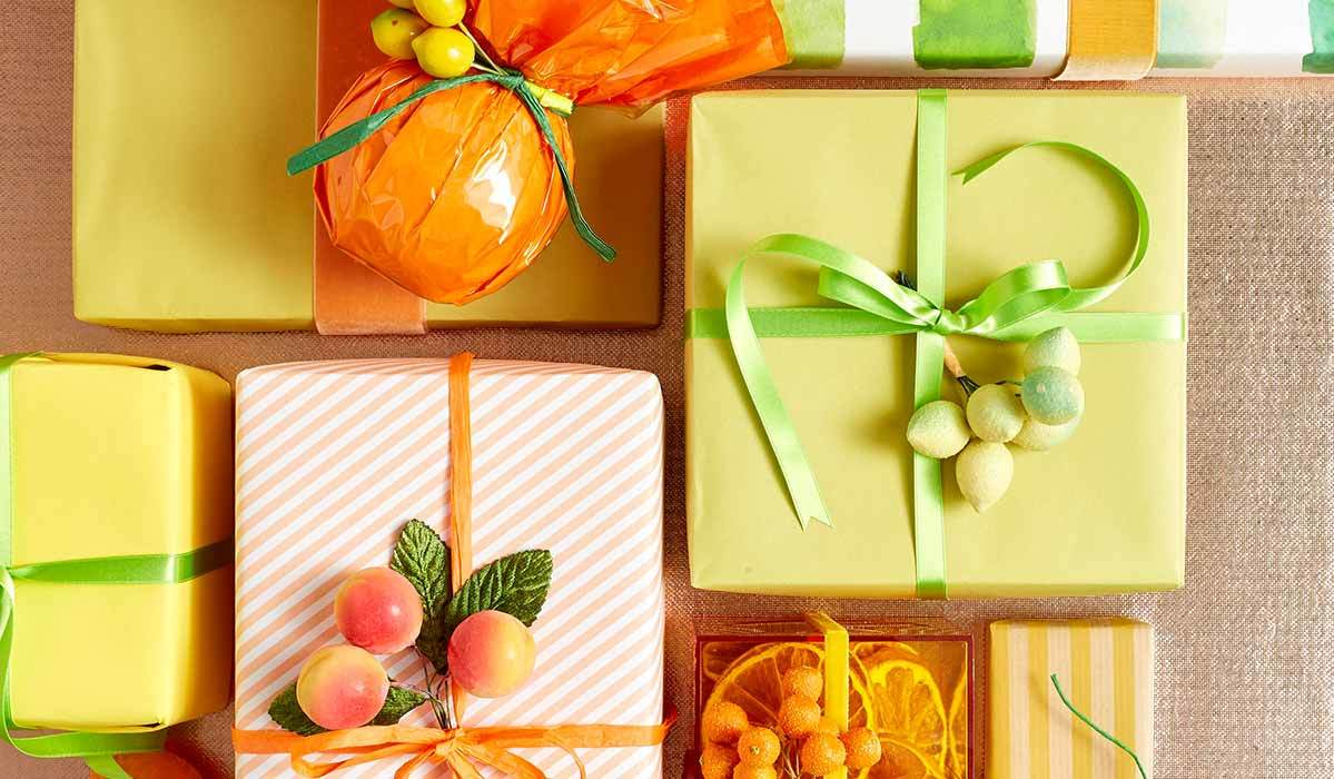Christmas gifts wrapped in orange and yellow paper with green ribbons photo