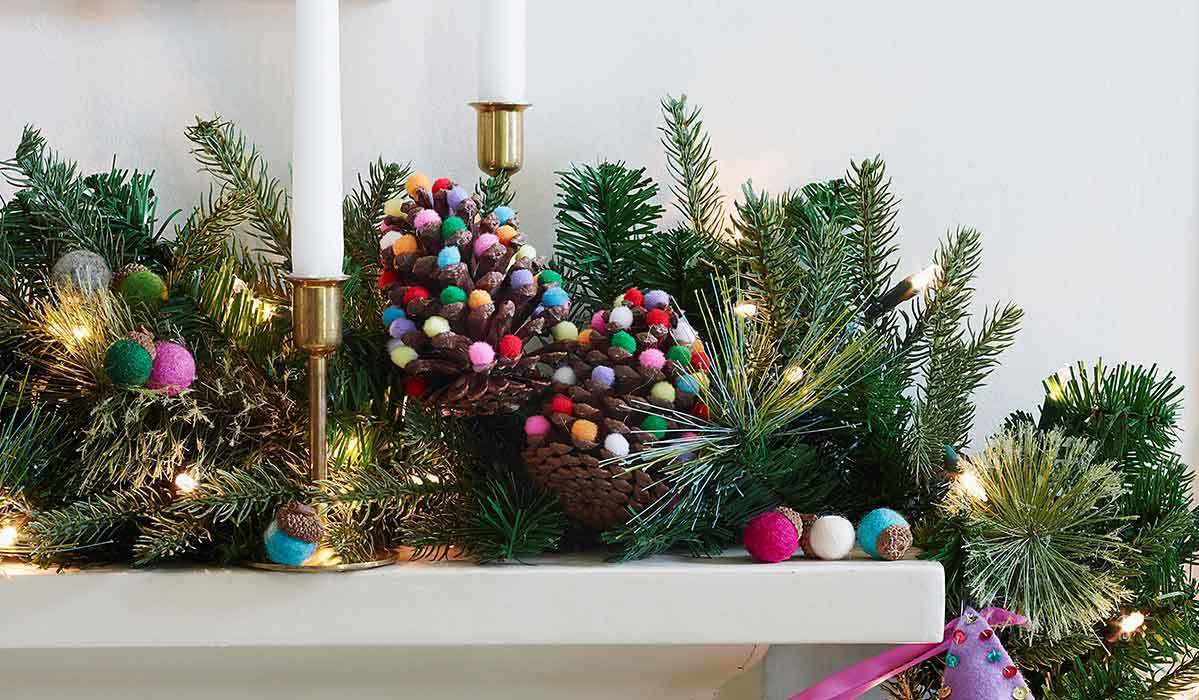 Mantel decorated with pine branches and jewel tone pom-poms photo