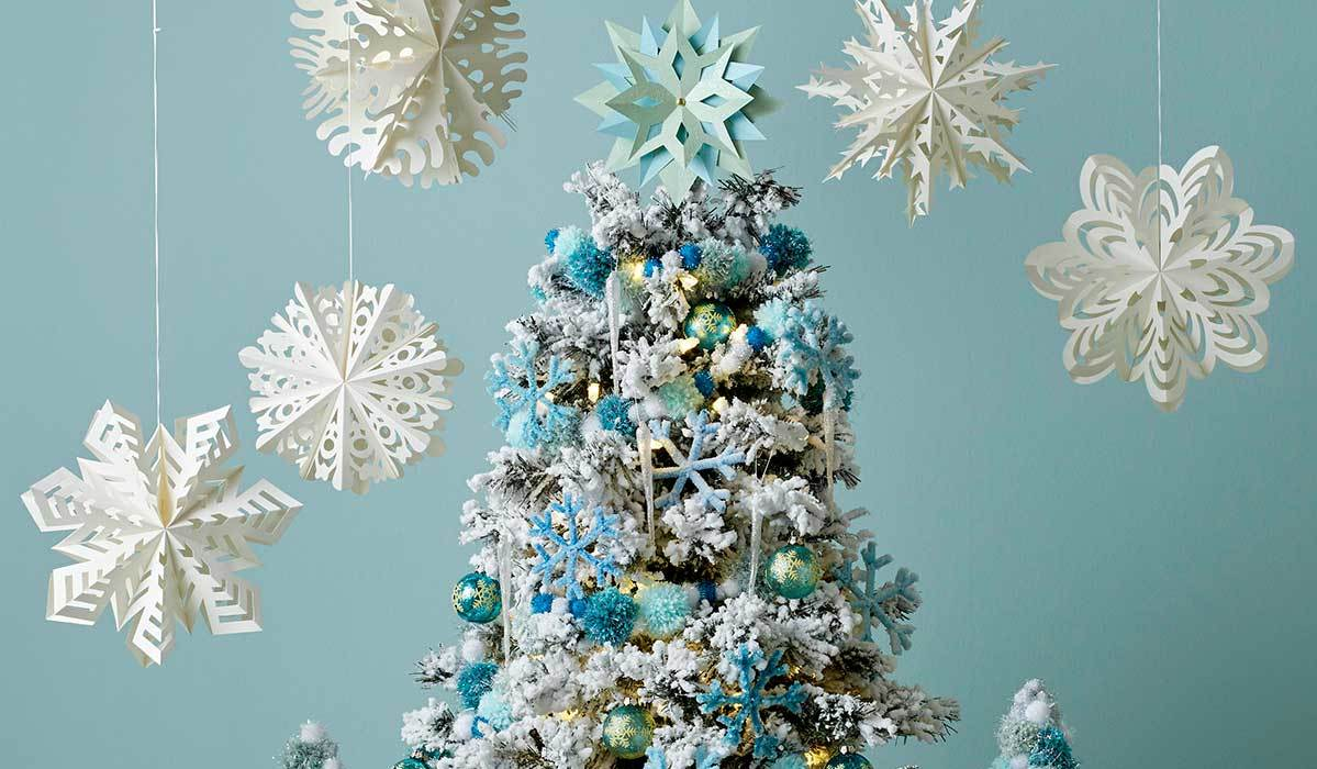 Blue and white christmas tree with paper snowflakes above it photo