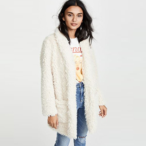 Model wearing tan, faux fur teddy coat with a graphic tee and jeans. photo