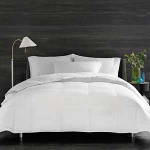 White comforter set by Real Simple with a standing lamp and night stand on the sides. photo