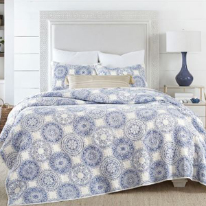 Blue and white coastal medallion quilt set with an off-white headboard and a lamp on a night stand next to the bed. photo