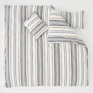 White, gray, and beige striped duvet cover set with the top right corner folded in to show the pillow underneath the bedding. photo