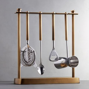 Set of five bar tools hanging on a gold rack. photo