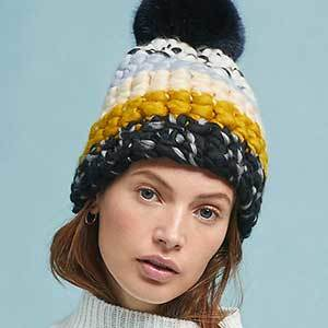 Black, yellow, white, blue chunky hat with a pom-pom on top. photo