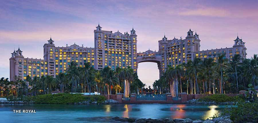 Atlantis Resort with palm trees in the foreground and a purple sunset in the background. photo