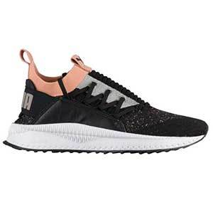 Black, white, and orange sneakers with laces on the side of the shoe photo