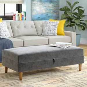 A gray ottoman is placed in front of a beige couch in a contemporary living room. photo