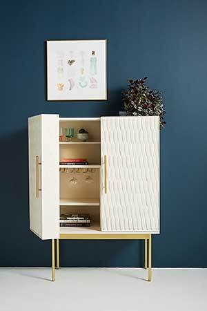 White bar cabinet with gold accents and a textured exterior. photo