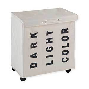 Beige canvas laundry bin with three compartments marked with words printed on the outside: dark, light, color. photo