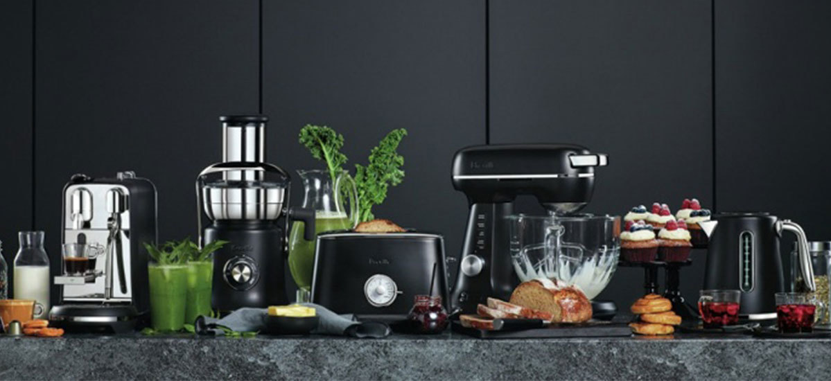 Kitchen appliances spread across a table with foods shown next to the coordinating kitchen tool