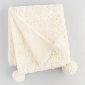 Ivory faux fur blanket with poms on the corners photo