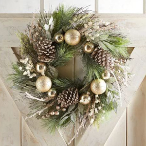 Green wreath with holiday ornaments, pine cones, and berries. photo