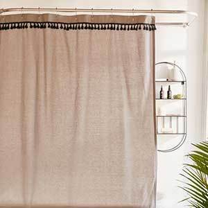 A gray colored shower curtain with small black tassels at the top. photo