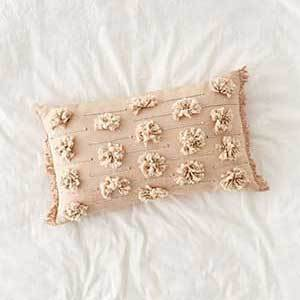 A rose colored throw pillow with tassels and pom-poms. photo