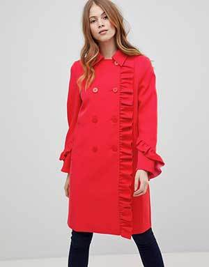 A woman wears a red peacoat with a ruffle down the front and down the sleeves. photo