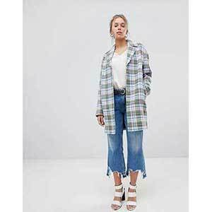 A woman wears a multicolored jacket with a check pattern. photo