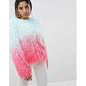 A woman wears a fluffy faux fur jacket with blue and pink ombre. photo