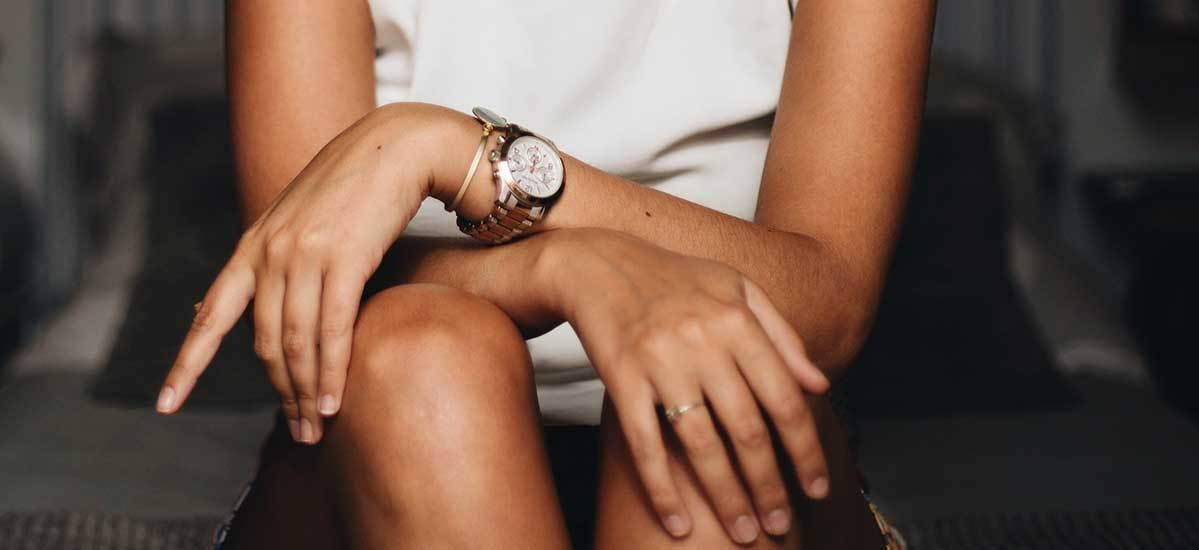 A woman in a white shirt wears a watch with her arms crossed