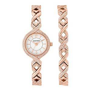 Rose gold metal watch with braided band and crystal details and a white face photo