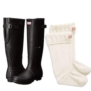 Tall white boot socks with a cable knit cuff and the Hunter logo on the front next to a pair of black hunter boots. photo