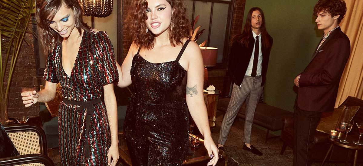 Two ladies dressed in sequin dresses with dramatic makeup at a holiday party