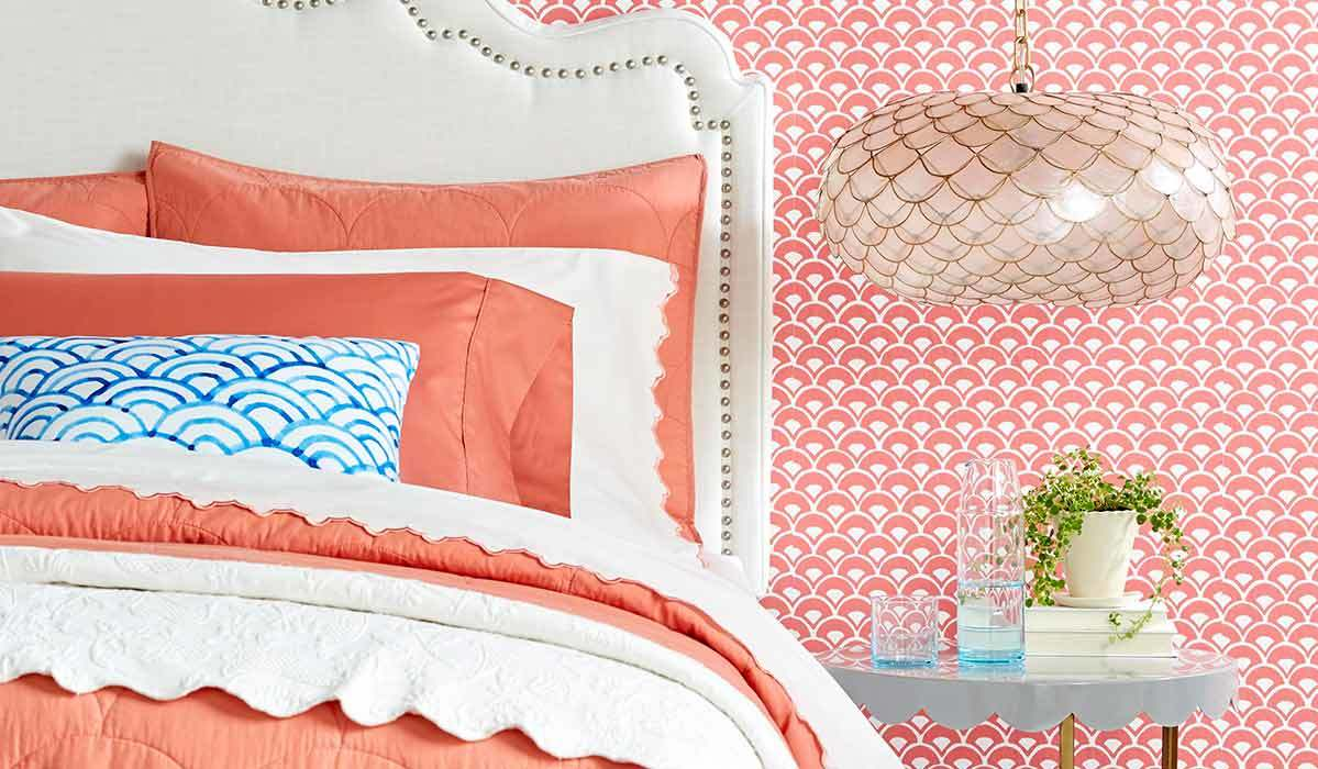 Bedroom with coral scalloped wallpaper, white headboard, blue and white pillow, and scalloped chandelier photo