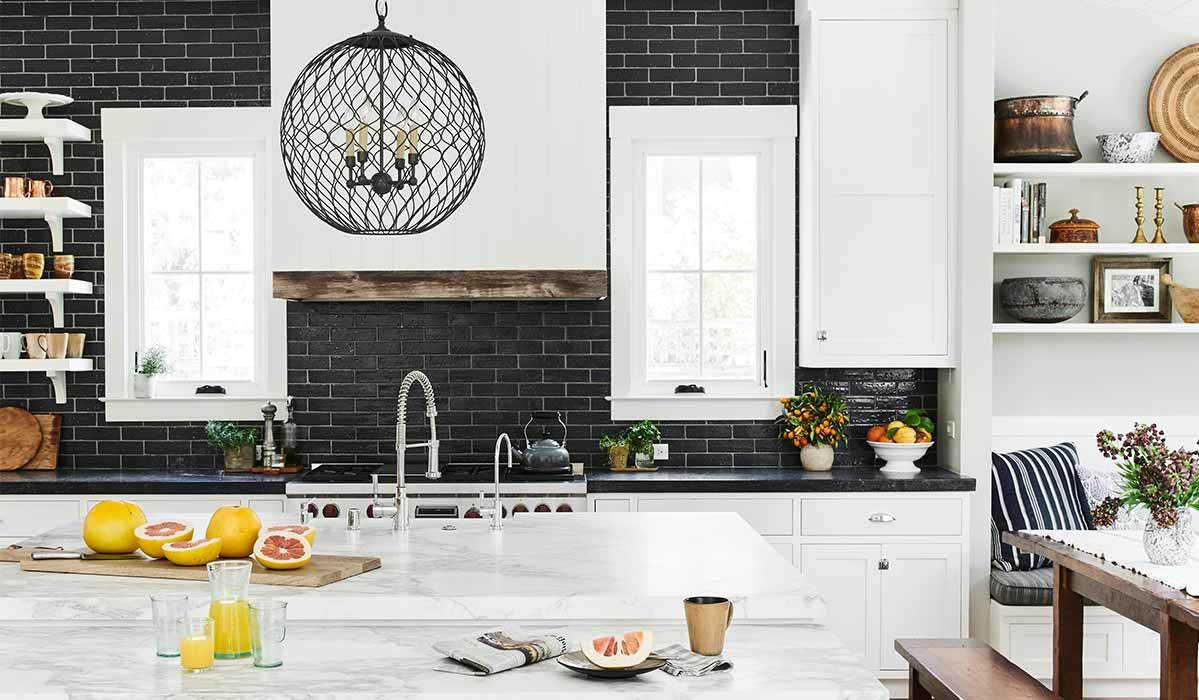 A monochromatic kitchen featuring marble counters, black tile, and decor. photo