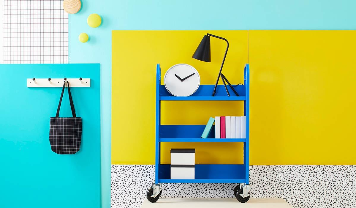 Colorful blue and yellow walls with decor like a book cart, lamp, clock, coat hanger, and more photo