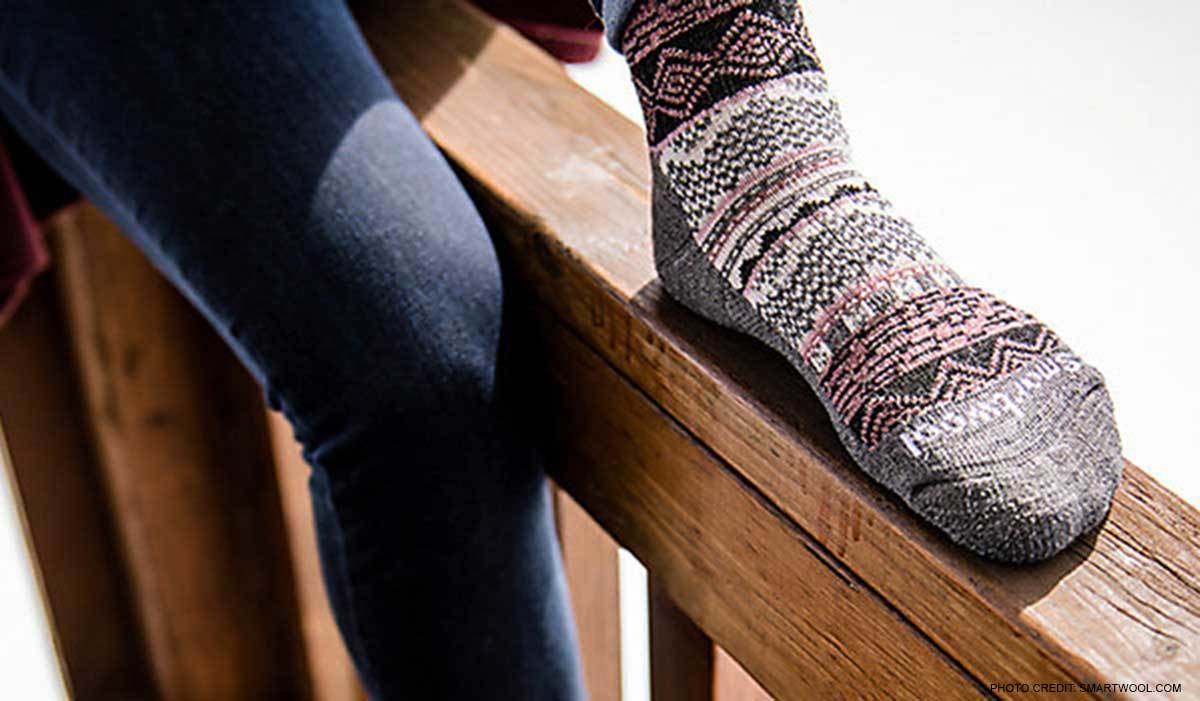 A person lounges outdoors wearing jeans and pink and gray patterned Smartwool socks photo