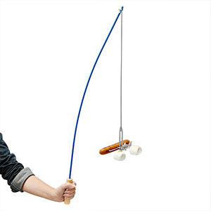 Person holding what looks like a fishing rod with a hot dog and two marshmallows on the end. photo