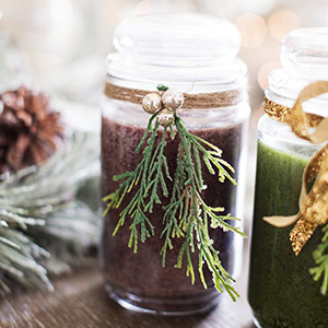 Burgandy candle with greenery accents attached. photo