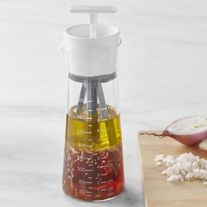 Glass salad dressing mixer with white measurements on the side. photo