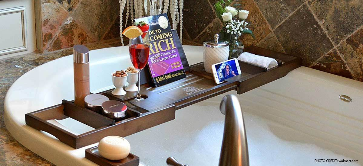 Bath caddy tray with retractable arms, wine glass stand, and book stand placed over a large bathtub