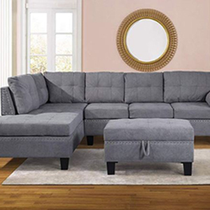 Living room with a gray sectional with chaise lounge and ottoman and a round wall mirror on the wall. photo