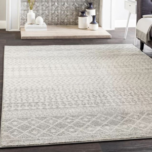 Gray and white distressed area rug with an aztec print on wood flooring. photo