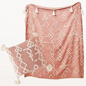 Rose pink throw pillow and blanket with a white aztec print and tassel detailing photo