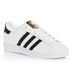 White Adidas sneakers with black stripes and gold accents photo