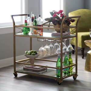 Gold bar cart with two shelves and a rack to hold wine glasses photo
