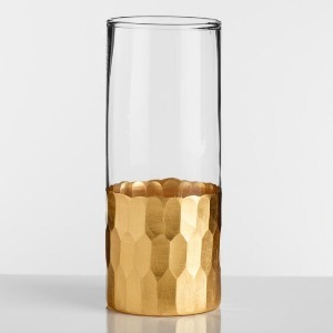 Tall, thin, clear glass with gold textured detailing along the bottom. photo