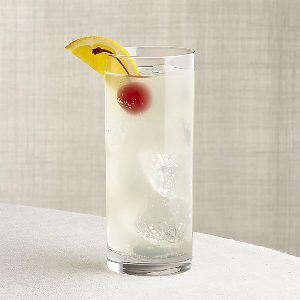 Tall, thin, clear glass with ice, a cocktail, a cherry and a lemon slice. photo