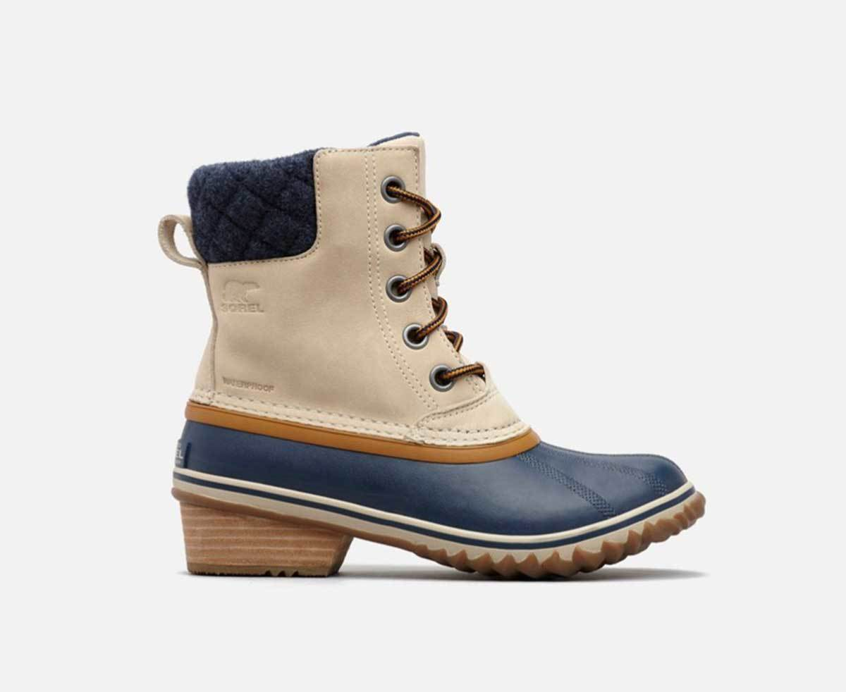 A profile view of the tan leather and navy blue rubber snow boots by Sorel. photo