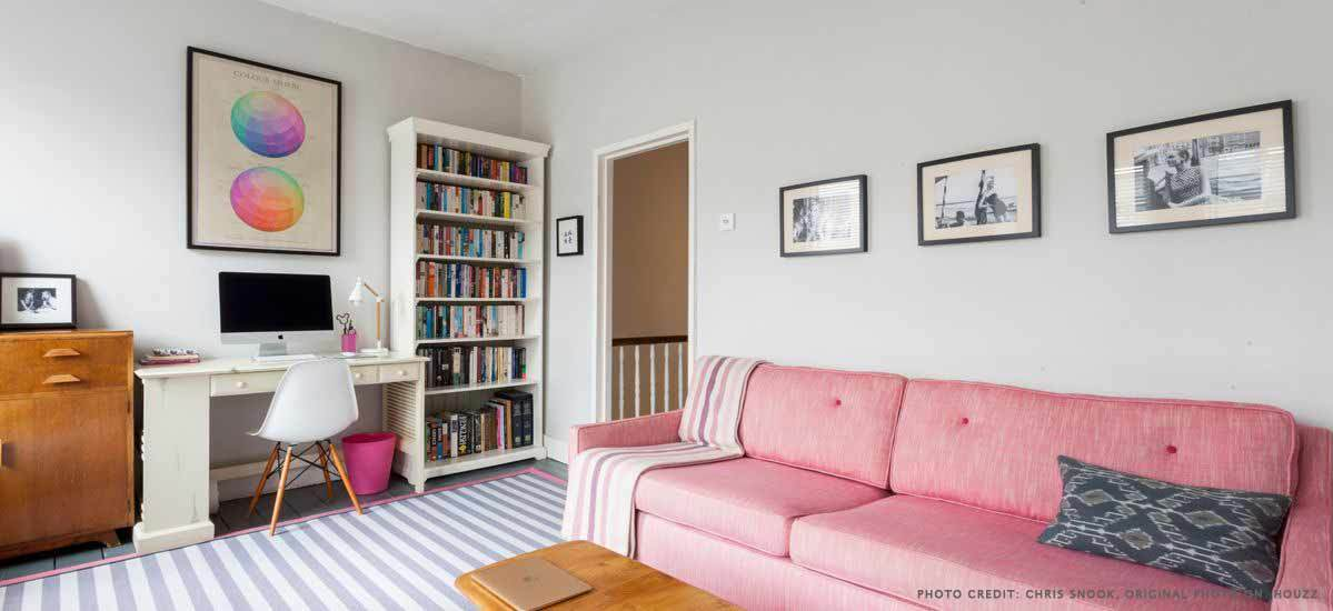 Living room with bright pink sofa and bookshelf.