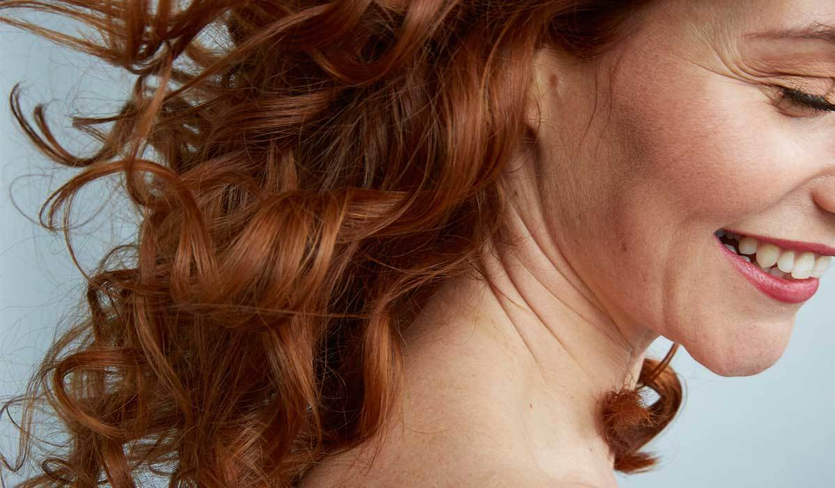 Smiling woman with red, curly hair photo