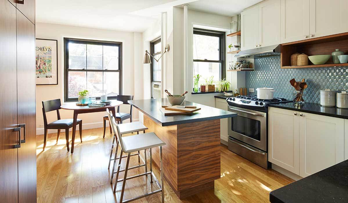 Modern-style kitchen with white barstools, wooden kitchen island, and white cabinets photo